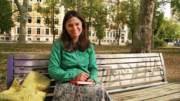 Amelie sitzt auf einer Parkbank und schreibt Tagebuch