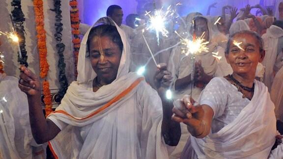 Indische Frauen tragen Wunderkerzen.