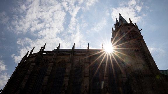 Die Sonne strahlt über der Silhouette des Doms, während im Dom der Gottesdienst zum Ostersonntag wegen des Coronavirus ohne Besucher stattfindet.