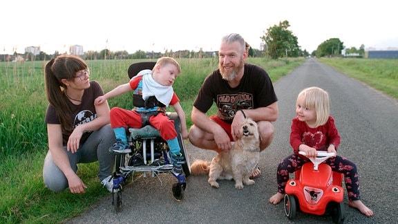 Ein Mann und eine Frau neben ihren Kindern; ein Junge sitzt im Rollstuhl