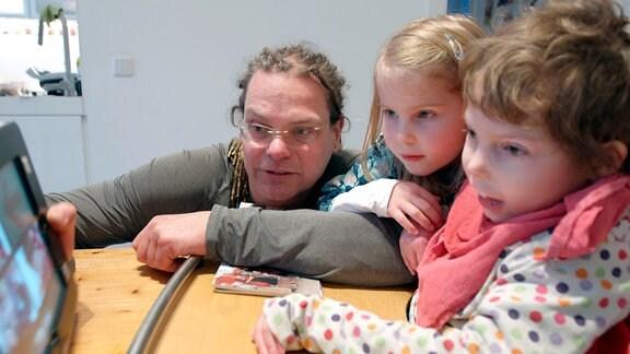 Ein Mann und zwei Kinder sehen auf ein Tablet