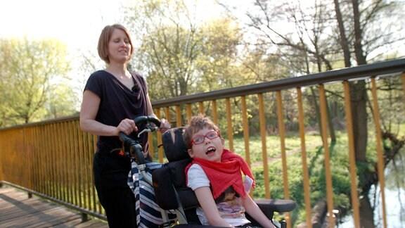 Ein Frau schiebt einen Jungen in einem Rollstuhl
