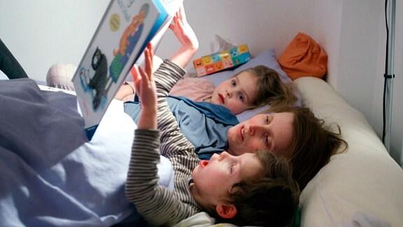 Eine Frau und zwei Kinder liegen in einem Bett und lesen in einem Buch