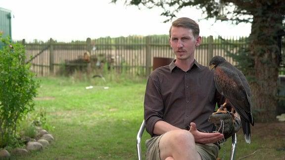 Der Falkner Leonhard Kindermann sitzt mit einem Falken auf dem Arm im Grünen.