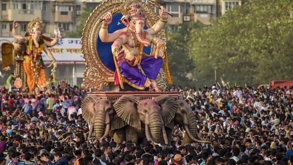 Gläubige tragen Abbilder des Gottes Ganesha.