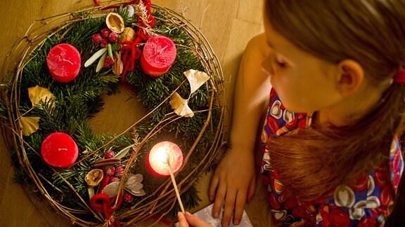 Kind zündet Kerze auf einem Adventskranz an