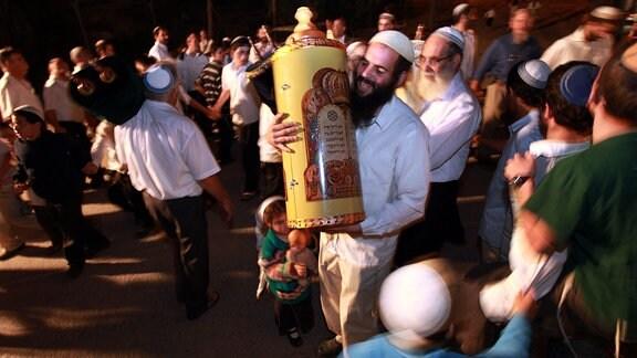 Ein kleines Mädchen hält 2009 eine Puppe und ihren Vater, der mit einer Torah-Rolle zwischen jüdischen Siedlern tanzt.