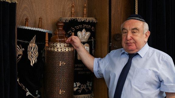 Ein Mann vor einem Schrank mit drei Schriftrollen