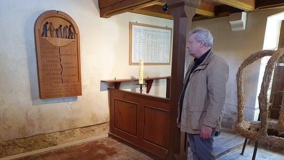 Pfarrer Hans-Michael Buchholz vor einer Gedenktafel in der Kirche von Gleicherwiesen