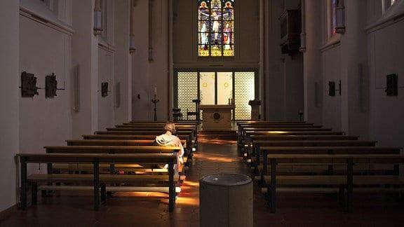 Eine Frau alleine in einer Kirche