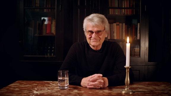 Bernd-Lutz-Lange. Ein Mann sitzt in einem abgedunkeltem Raum an einem Tisch und schaut in die Kamera. Vor ihm stehen eine Kerze und ein halbvolles Glas mit Wasser.