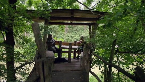 Zwei Personen sitzen in einem Baumhaus.