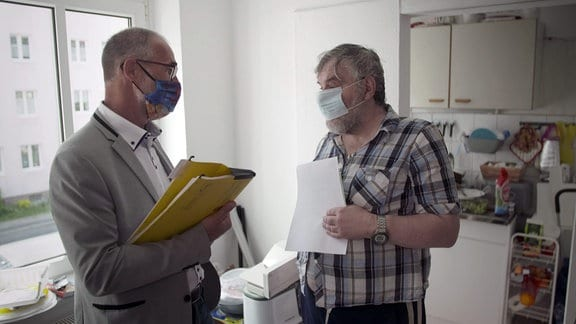 Zwei Männer stehen mit Mund-Nasen-Maske in einer Wohnung.
