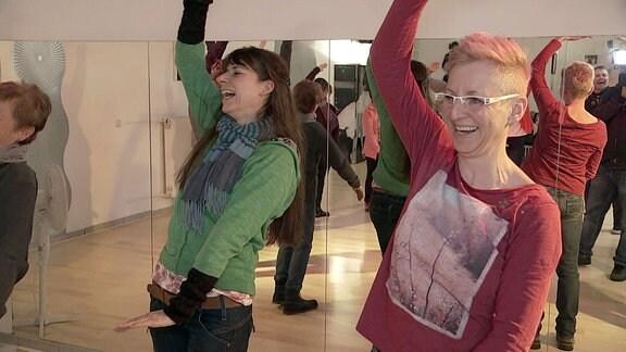 Menschen lachen gemeinsam bei einem Yoga-Kurs.