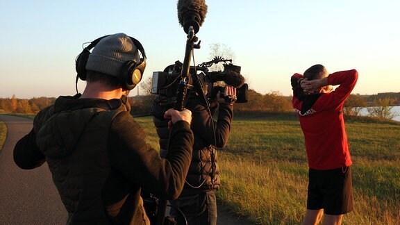Filmteam filmt Mann von hinten
