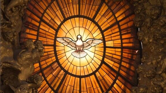 Ein Kirchenfenster mit einer Darstellung des Heiligen Geistes in Form einer Taube.