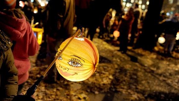 Kinder ziehen beim Sankt-Martins-Umzug mit Laternen durch die Straßen