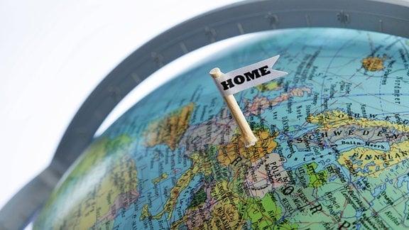 """Ein Fähnchen mit der Aufschrift """"Home"""" steckt bei Deutschland auf einem Globus"""