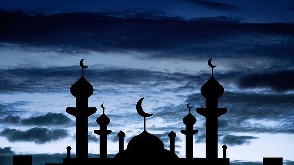Minarette einer Moschee zeichnen sich als Schatten vor einem dunklen Himmel mit Halbmond ab.