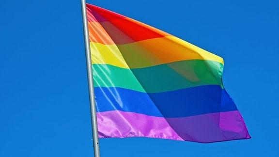 Eine Regenbogenfahne vor blauem Himmel