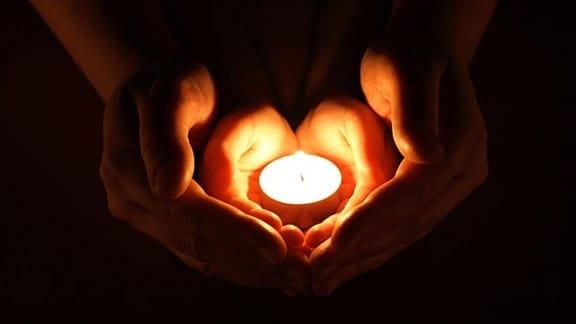 Vier Hände um eine Kerze.