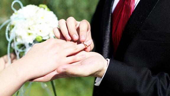 Ein Bräutigam steckt einer Braut einen Ring an den Finger