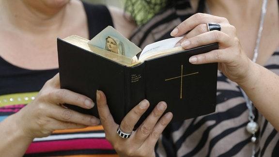 Zwei Frauen halten gemeinsam eine Bibel.