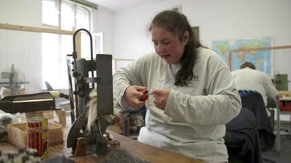 Junge Frau arbeitet in Werkstatt.