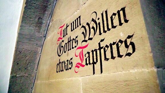 """Das an die Wand gemalte Zitat von Ulrich Zwingli: """"Tut um Gott's Willen etwas Tapferes""""."""