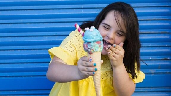 Mädchen mit Downyndrom hält eine Eiswaffel