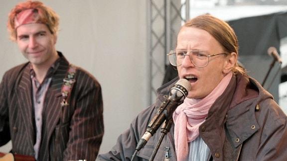 Ein Mann steht am Mikro und singt.