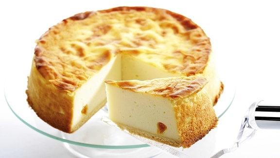 Frischer Käsekuchen wird angeschnitten.