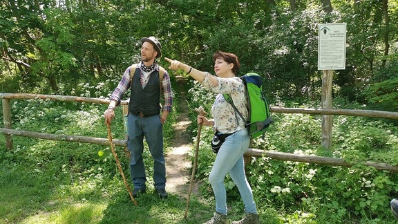 zwei Menschen stehen am Waldrand auf einer Wiese