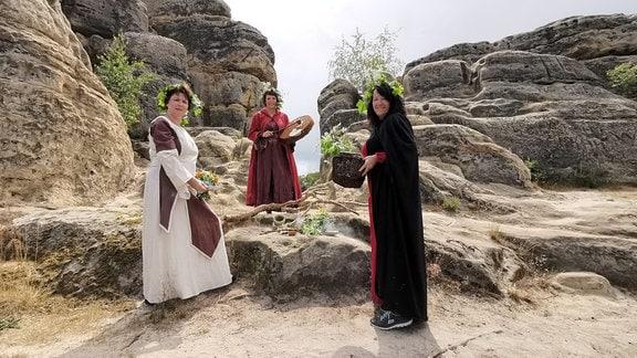 drei Frauen in mittelalterlichen Gewändern am Fuße der Klusberge