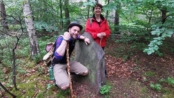 ein Mann hockt und eine Frau steht an einem Stein