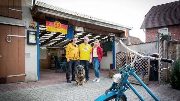 Drei Menschen und ein Hund vor einem Carport mit DDR-Fahne.