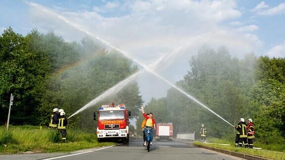 Eine Frau und ein Mann fahren mit ihrem Tandem durch Wasserfontänen der Feuerwehr, darüber strahlt ein Regenbogen.