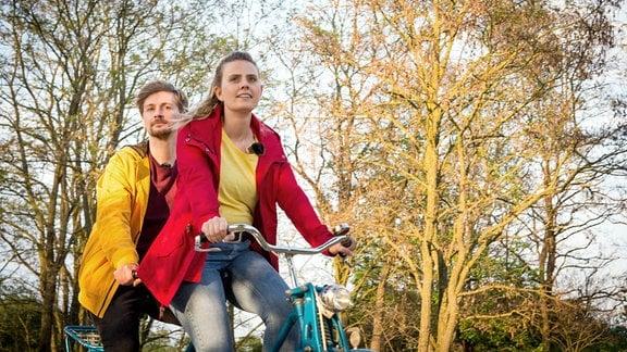 Eine Frau und ein Mann fahren mit ihrem Tandem durch die Natur.