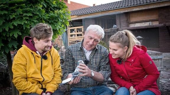 Eine Frau und ein Mann sitzen neben Mann, der Taube in der Hand hält.