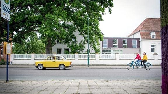 Gelber Trabant auf Straße, dahinter strampeln Mann und Frau auf Tandem.