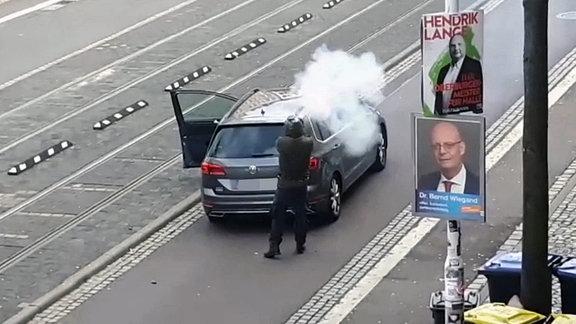 Ein Mann hinter einem Pkw feuert eine Waffe ab