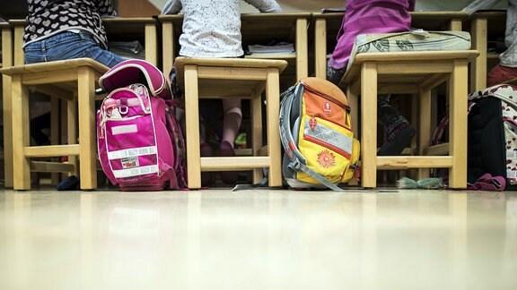 Zwei Schulranzen stehen auf dem Boden eines Klassenzimmers