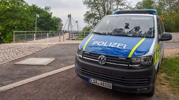 Ein Polizeiauto steht vor einer Brücke in Magdeburg