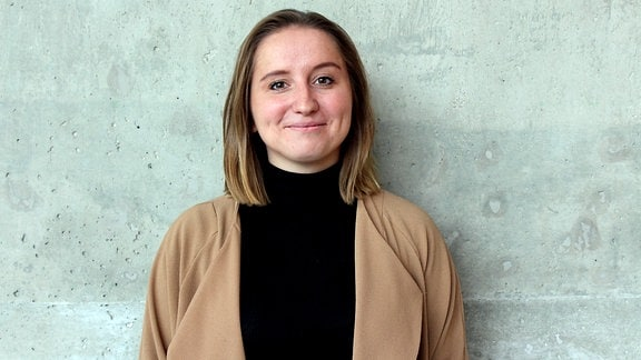 Eine junge Frau mit schulterlangem Haar und senffarbener Strickjacke steht vor einer Betonwand