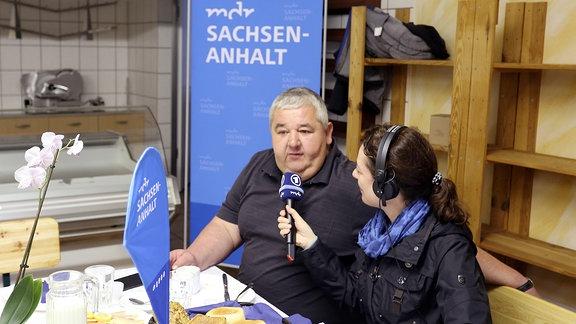 Eine Frau mit Pferdeschwanz interviewt am Frühstückstisch einen Mann im Polo-Shirt