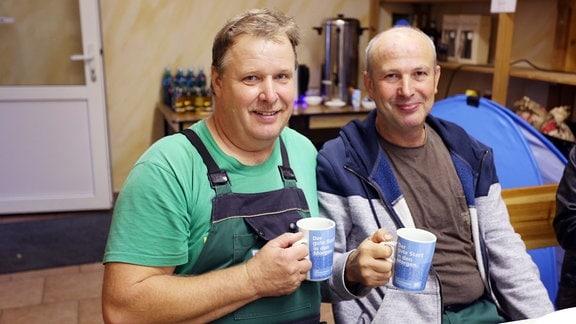 """Zwei Männer lächeln in die Kamera und halten Tassen mit dem Schriftzug """"Der gute Start in den Morgen"""" hoch"""