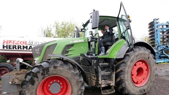 Eine Frau und ein Mann sitzen in einem grünen Traktor