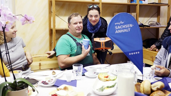 An einem Frühstückstisch sitzen mehrere Personen, eine Frau mit Schaltuch überreicht einem Mann ein orangenes Radio