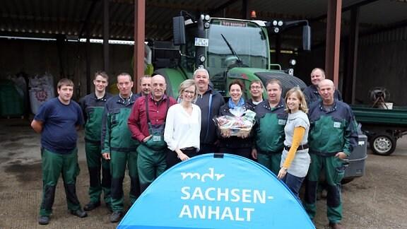 Eine Gruppe Männer und Frauen, überwiegend in grüner Kleidung, stehen vor einem Traktor