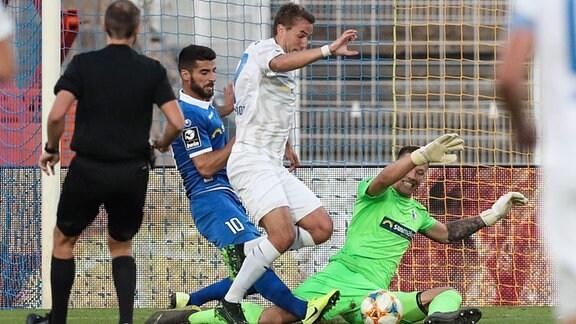 Julian Günter Schmidt (FC Carl Zeiss Jena) gegen Torwart Alexander Brunst und Jürgen Gjasula (1. FC Magdeburg).